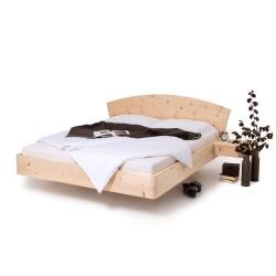 Zirbenbett mit halbrundbogenkopfteil und rundecken. Arvenbett mit Nachtkästchen.